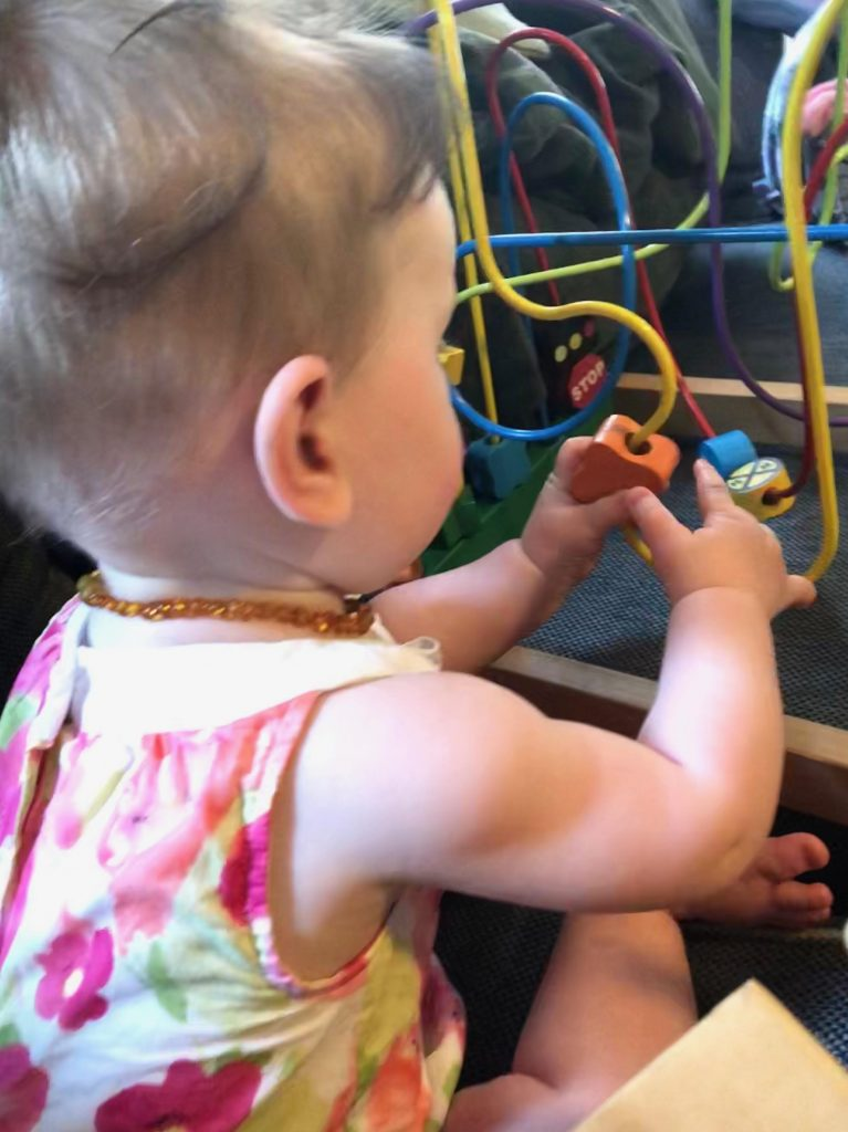baby playing with bead maze