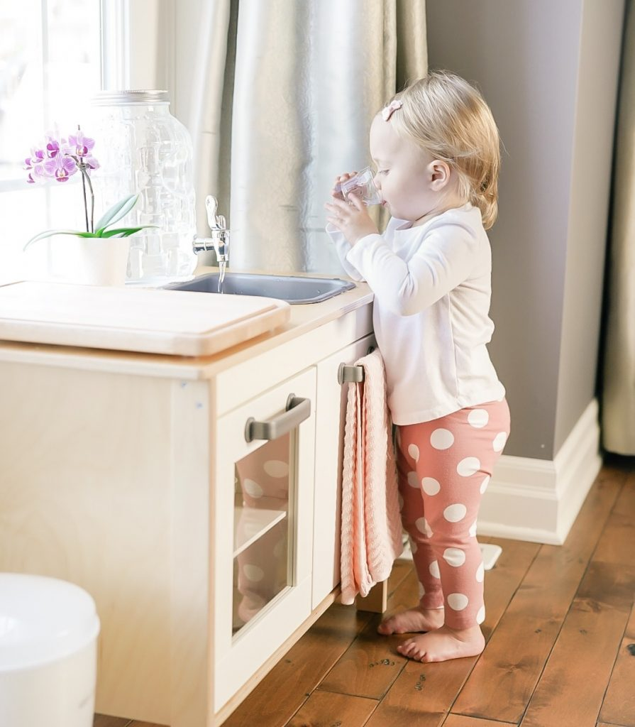 child drinking from glass at Montessori at home ikea kitchen.