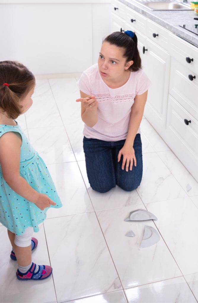 mother punishing child for breaking dish. No discipline.