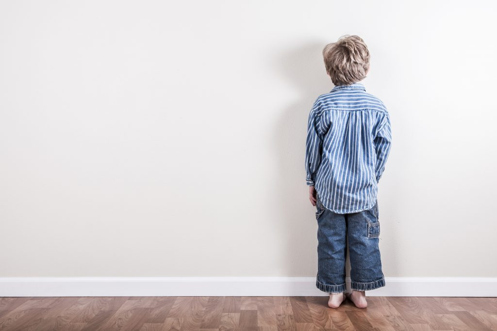 child in time-out facing wall, natural consequences vs. punishment.