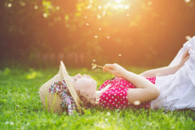 child laying in the grass, blowing dandelion,