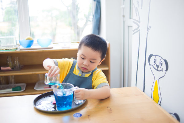 child pouring water from small glass to large glass