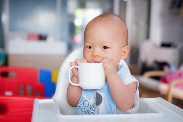 Baby drinking from glass mug