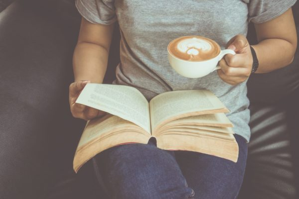 What Montessori Book Should You REad First? image of woman reading Montessori book with coffee.
