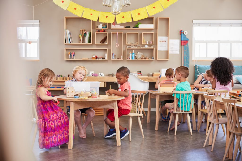 children working obediently in a prepared environment Montessori classroom.