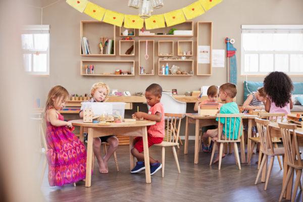 children working obediently in a prepared environment Montessori classroom.