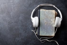 Headphones covering book to represent audiobook. Audiobooks and vocabulary.