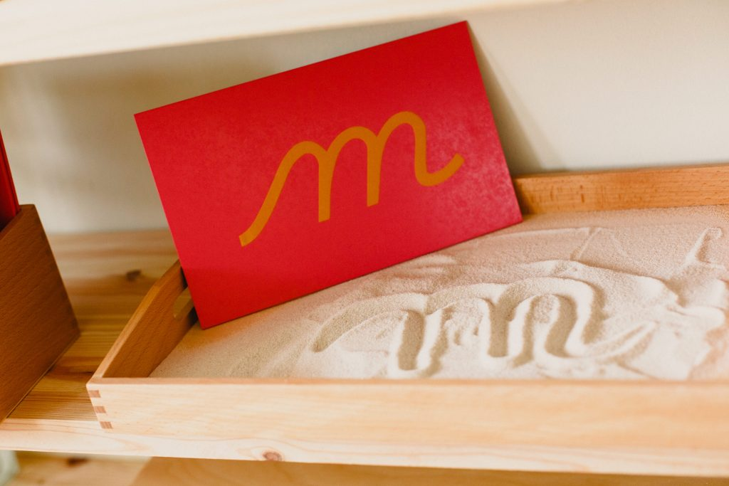 """Montessori cursive letter """"M"""" and sand tray with letter written in sand. one way Montessori education works by teaching writing."""