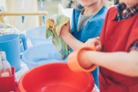 When Montessori Started: children washing dishes a practical life skill, which is sometimes a montessori criticism.
