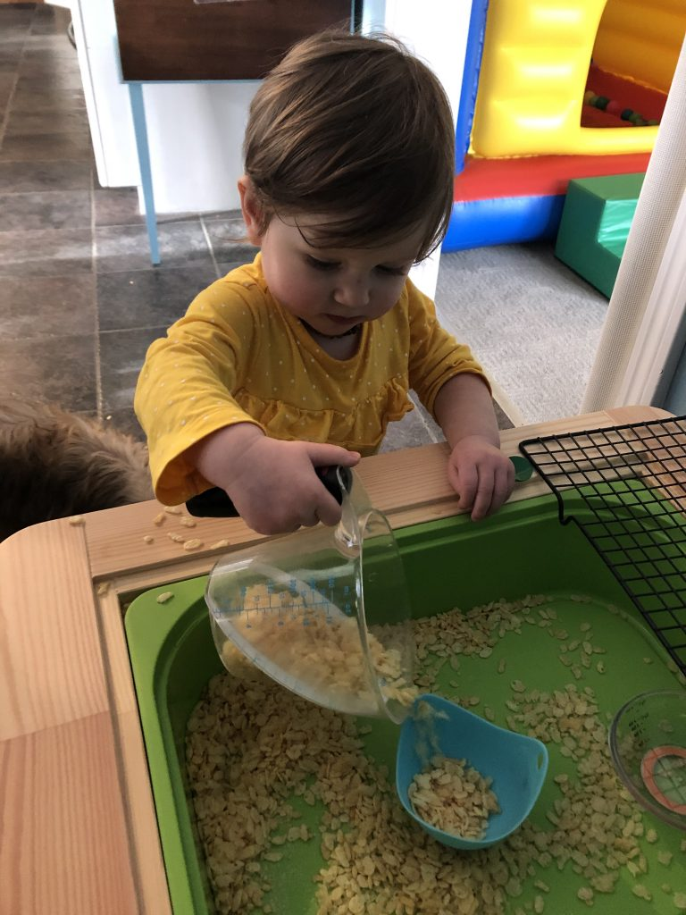 toddler pouring cereal in sensory play table.