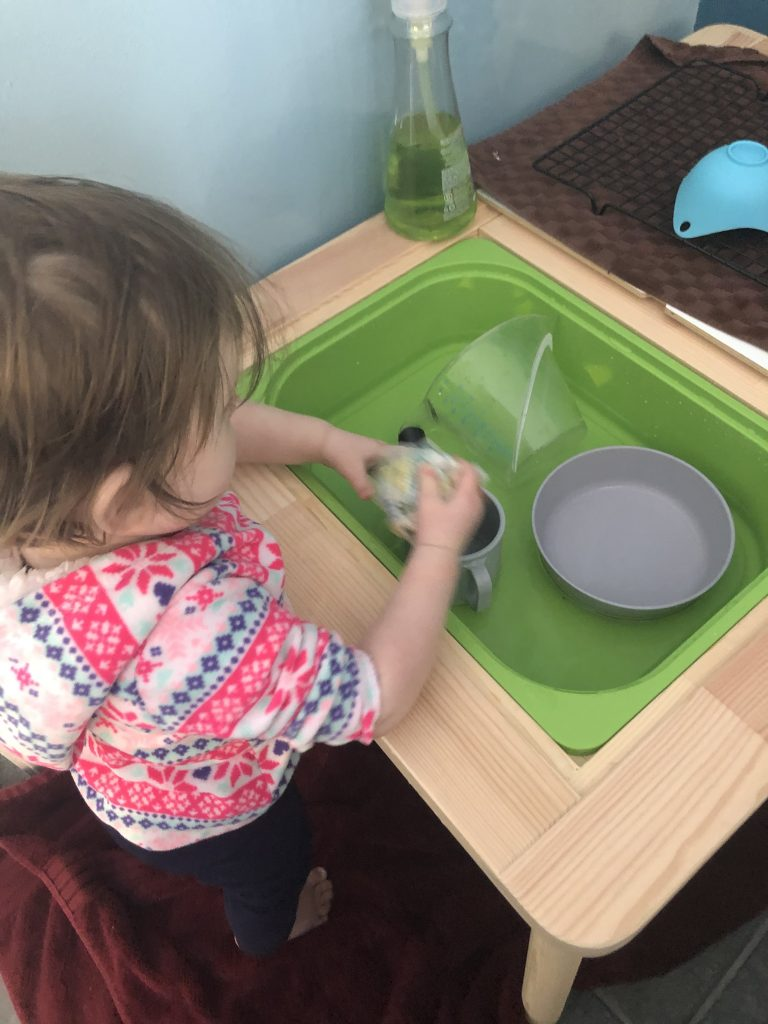 Toddler Dishwashing in sensory play table.