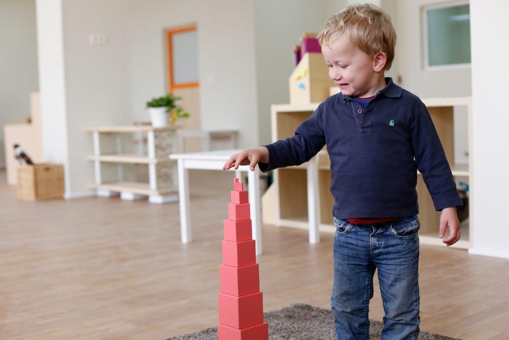 Boy building Montessori Pink Tower, showing normalization in montessori.