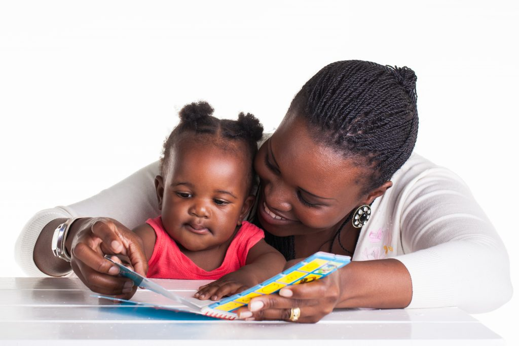 Why reading to newborns is beneficial, image of mother reading to baby.