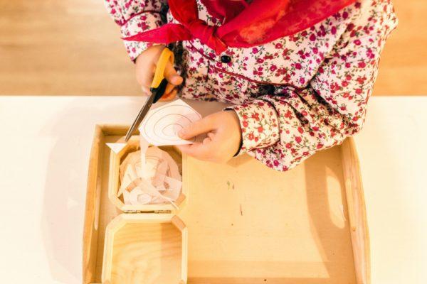 Child cutting paper in Montessori school. Montessori-like schools