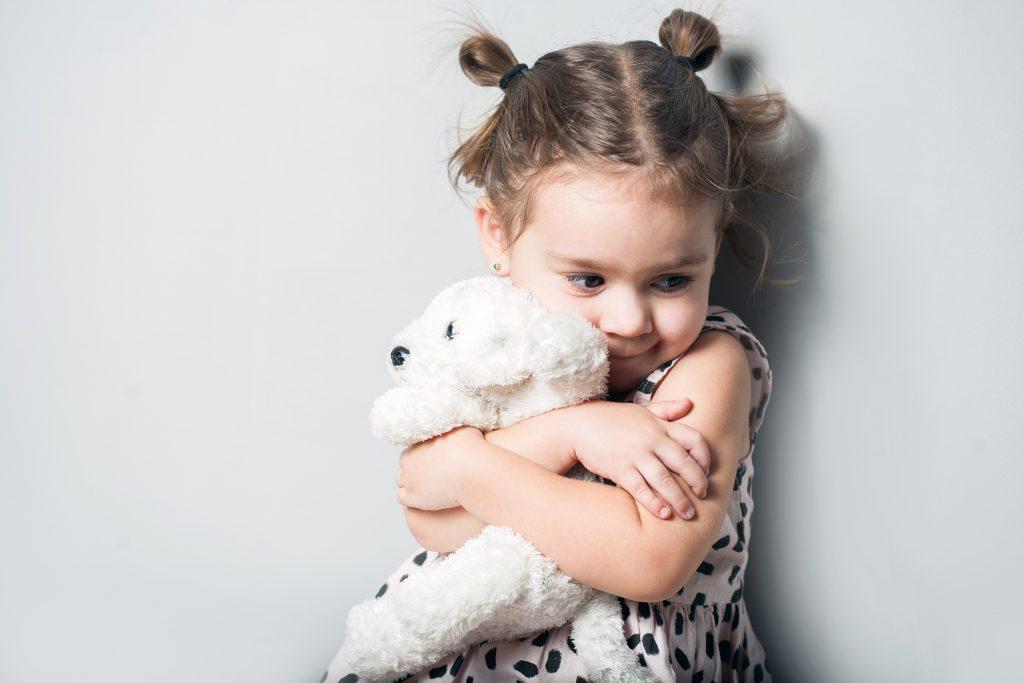 Child Hugging Stuffed Animal.
