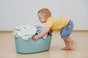 child doing heavy work by pushing laundry basket.
