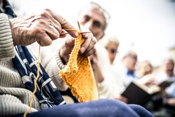 Montessori in Nursing Homes, an older person knitting, a fine motor skill activity.