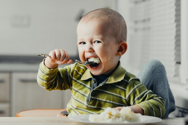 Baby eating with a spoon.