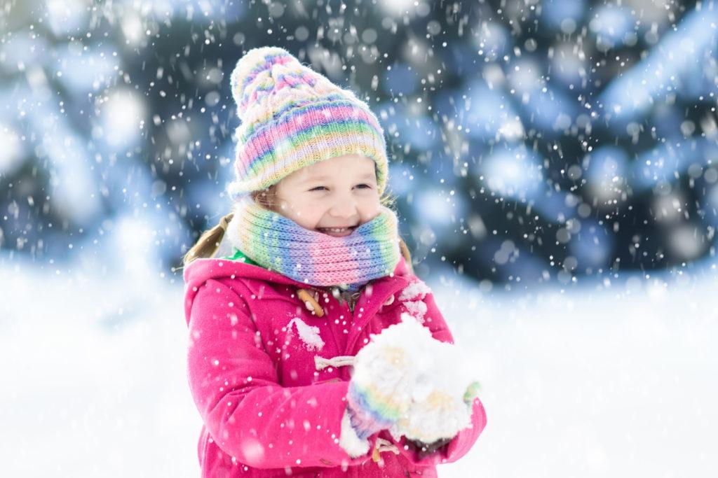 girl outside in snow wearing winter coat.