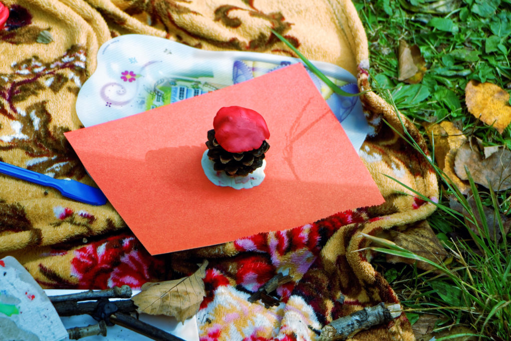 loose parts play image of pinecone, playdoh and glue on piece of red paper.