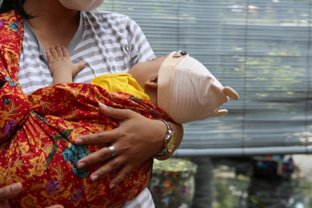 Woman babywearing using sling.