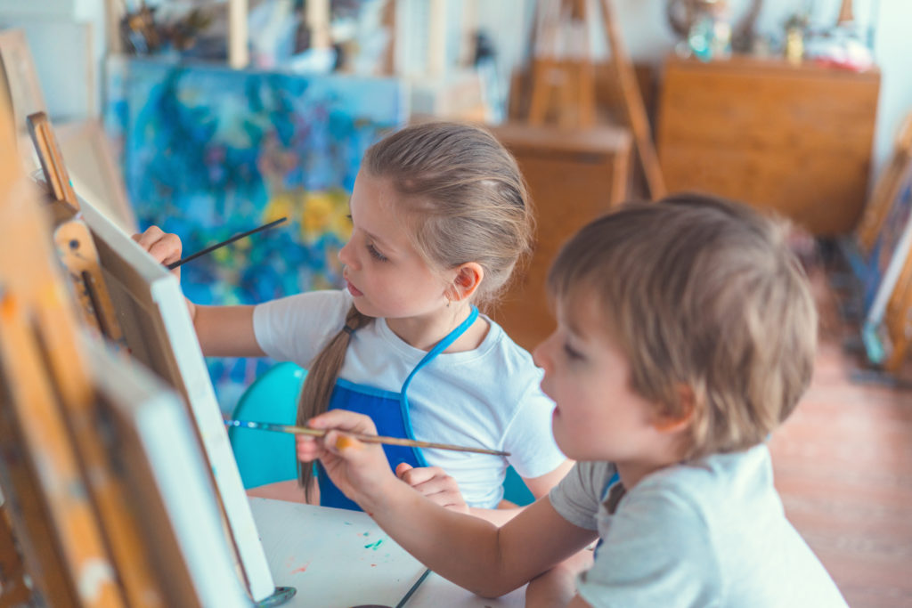children painting on easels in art area for toddlers.