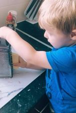 Toddler using cheese grater