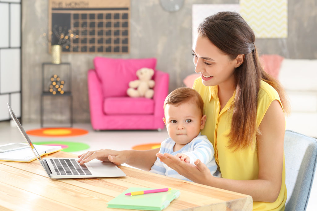 Woman with baby on lap, looking through Montessori blogs.