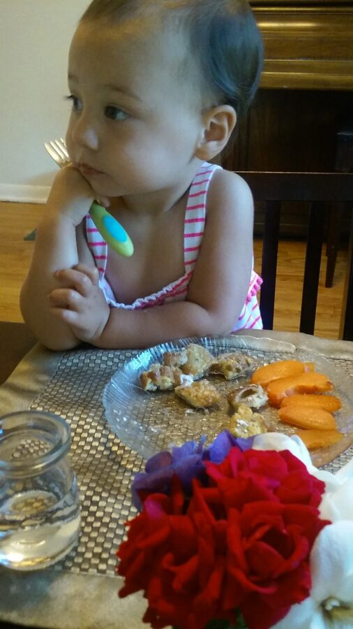 child sitting at Montessori weaning table eating.