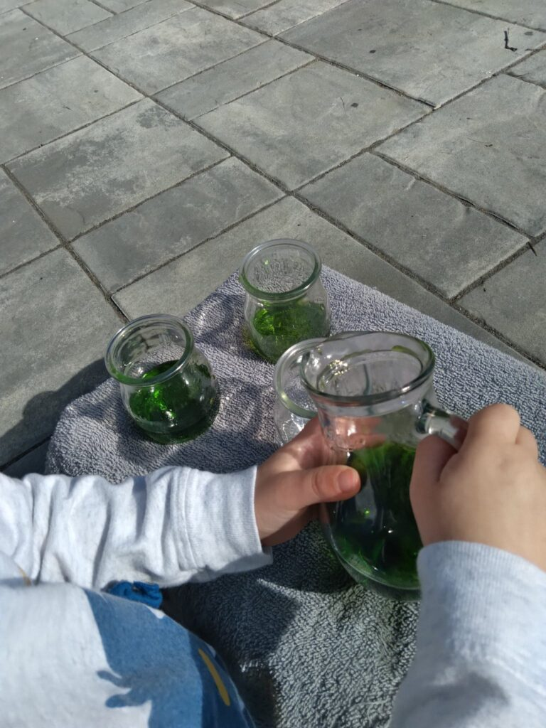 child pouring water from glass pitcher to glasses.
