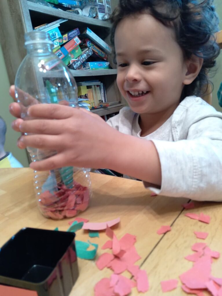 child smiling and looking at bottle of torn paper.