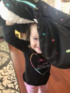 Toddler proudly learning how to put on a coat, by flipping it over their head.