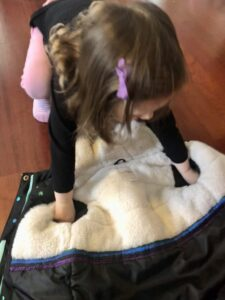 toddler learning how to put on a coat by putting arms through sleeves, coat is on ground upside down.