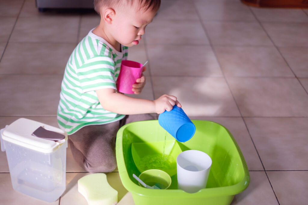 child washing dishes as a practical life activity for Montessori on a budget.