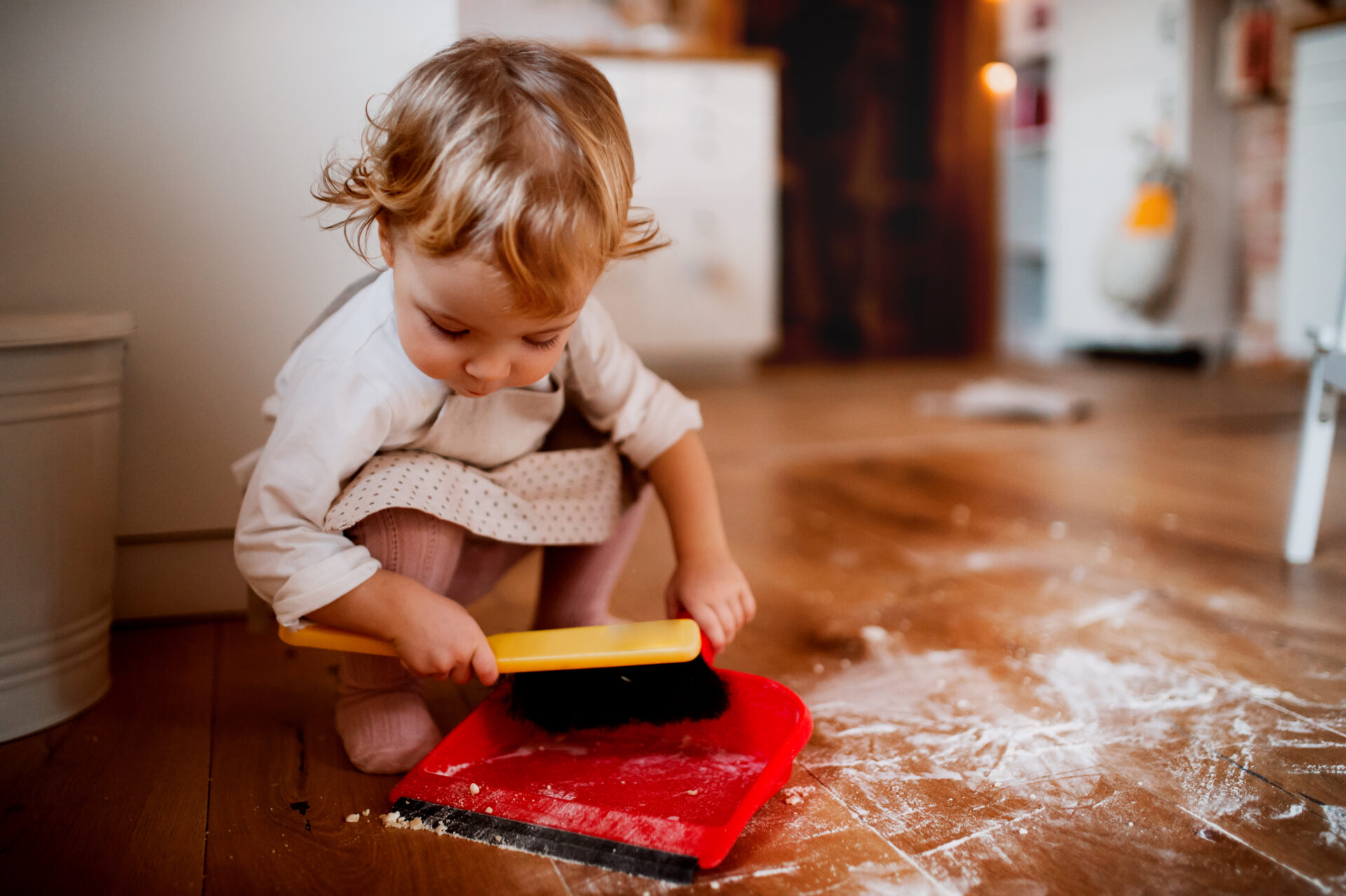 child sweeping up flour from floor as part of natural and logical consequences.