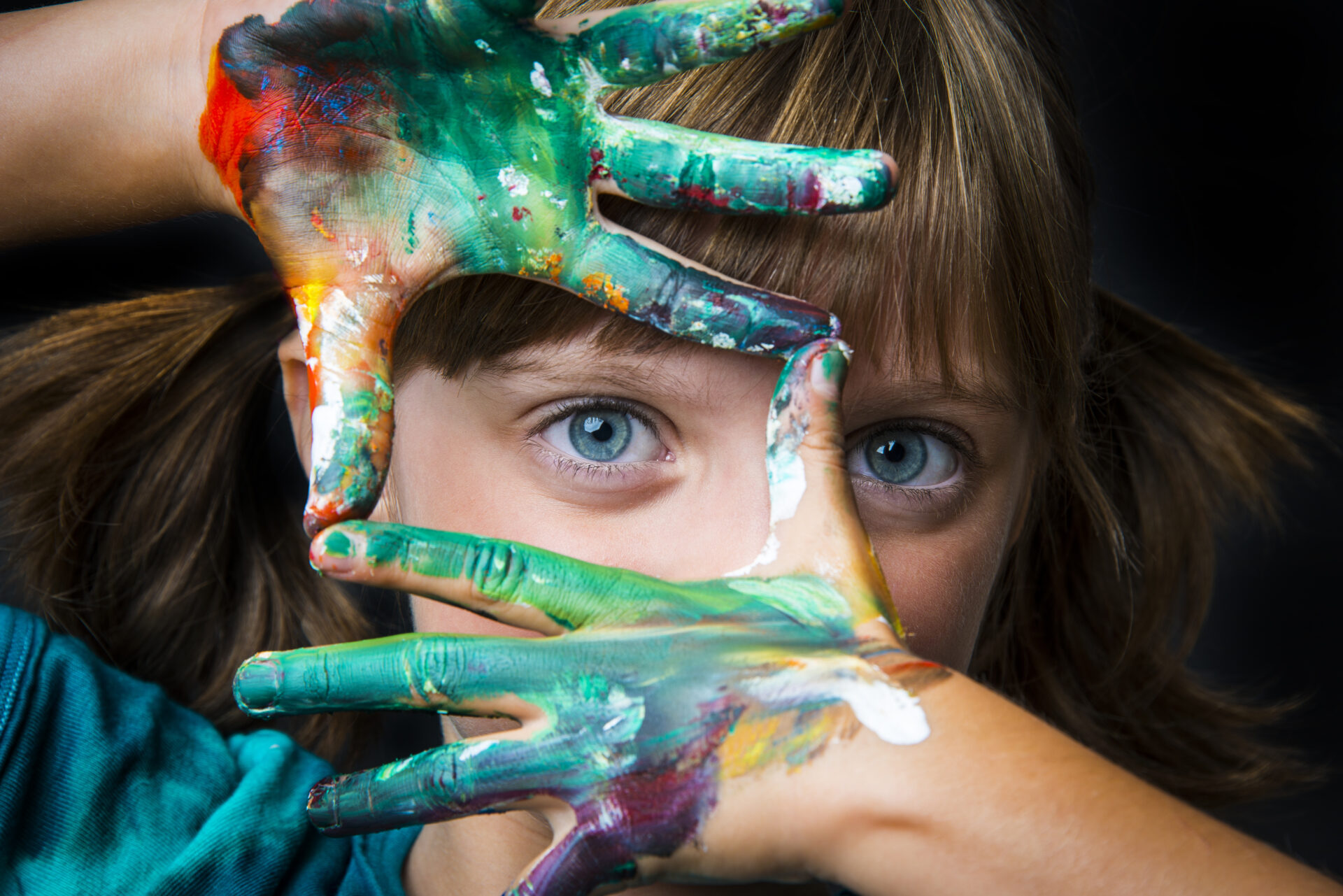 child being creative with paint on her hands.