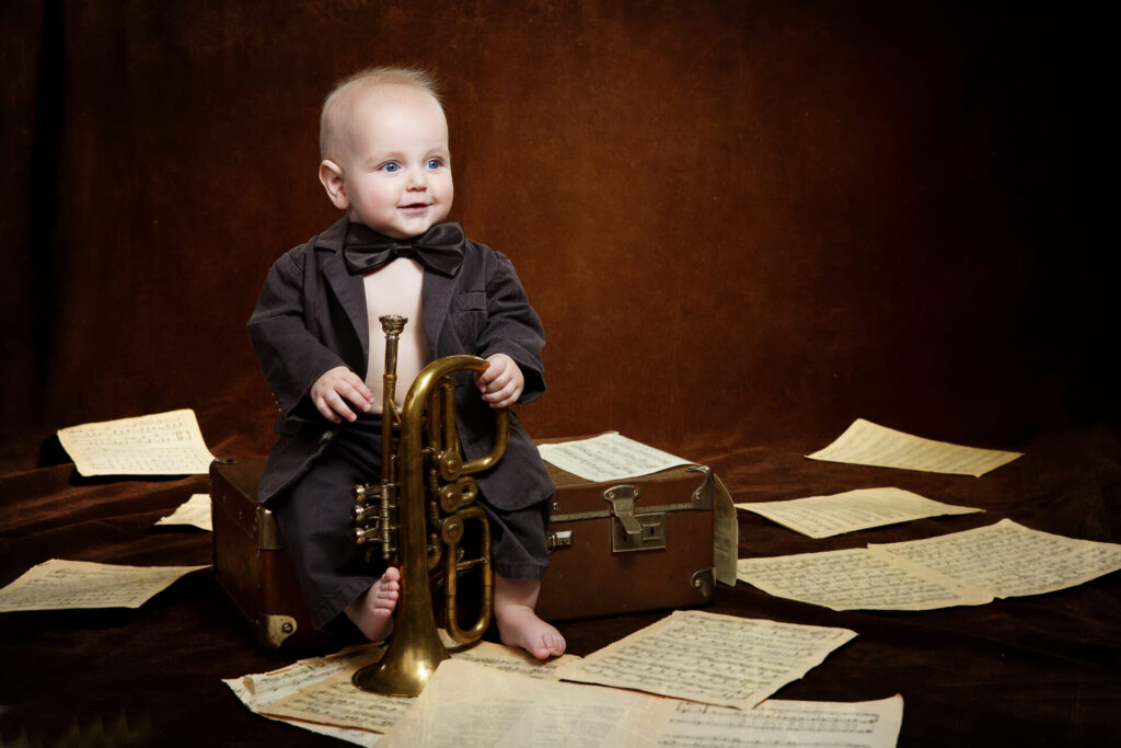 child sitting with horn and music.