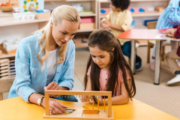 good montessori teacher working with kids.
