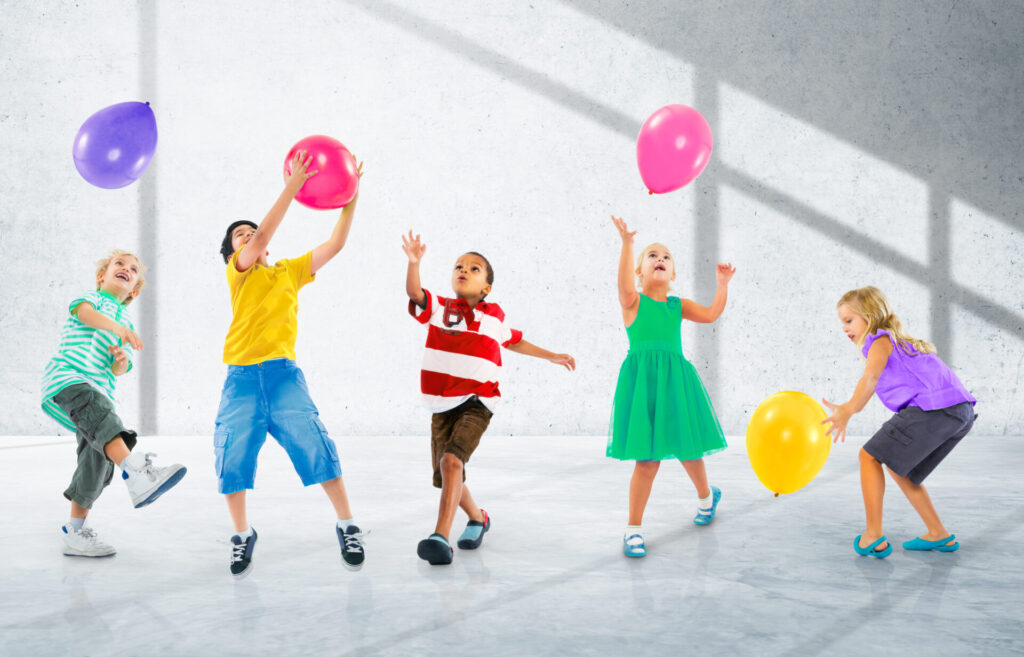 kids moving to the music and playing with balloons.