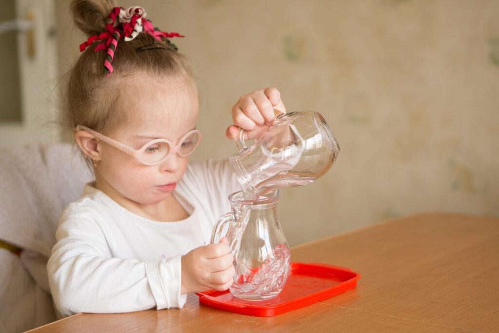 child doing montessori water pouring activity.