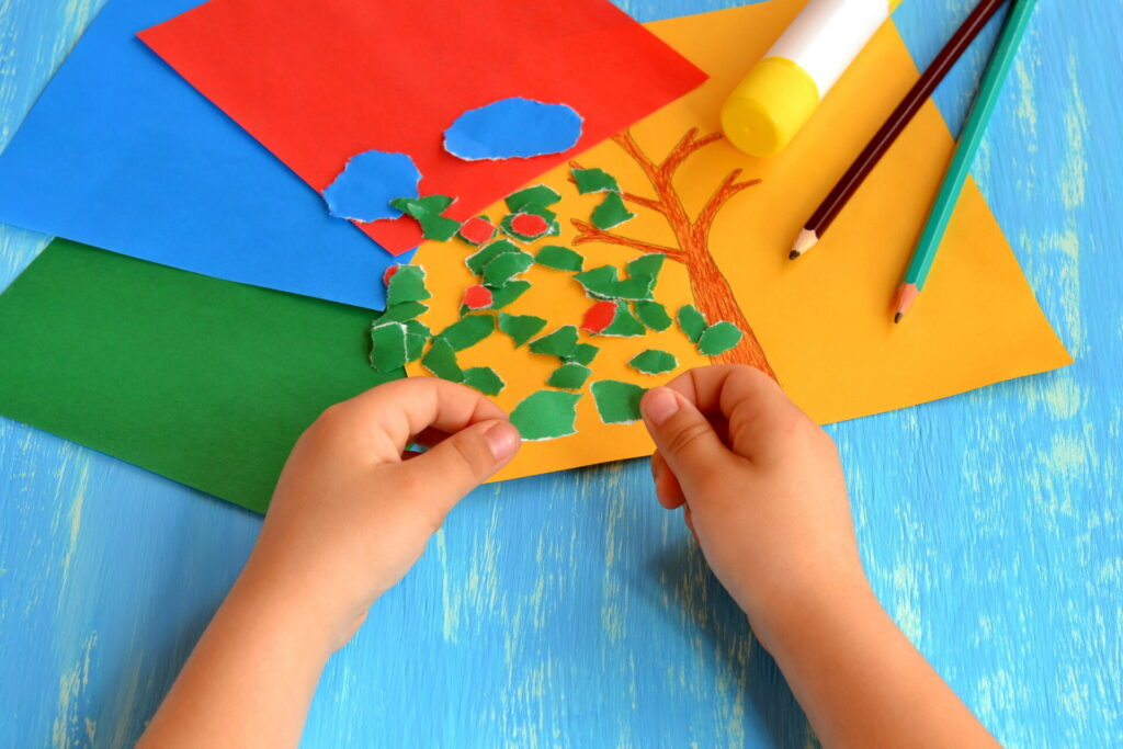child tearing paper for montessori paper tearing activity.