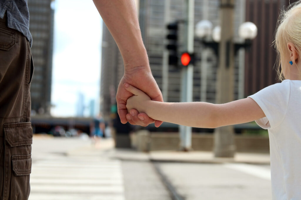 child holding father's hand while crossing the street.