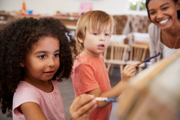 good montessori teacher watching children paint.
