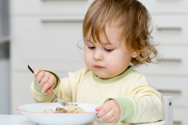 child eating with real dishes at montessori weaning table.