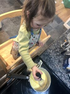 Toddler mixing cornmeal on stove for Fry Bread.