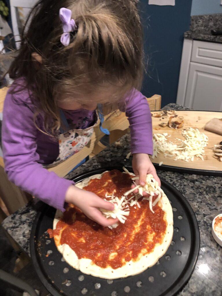 Toddler putting mozzarella on pizza.