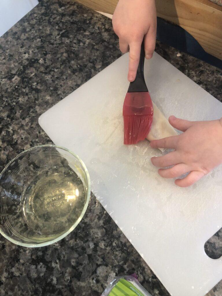 Toddler brushing egg wash on wonton wrapper for dim sum.