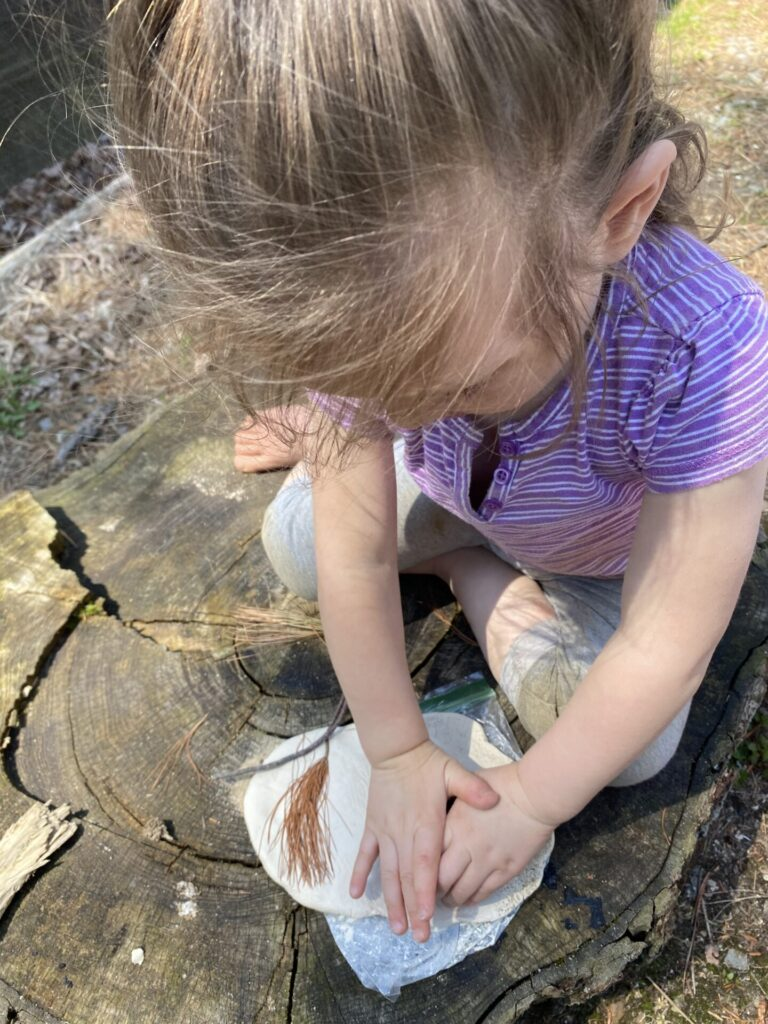 toddler pressing nature materials in air dry clay.
