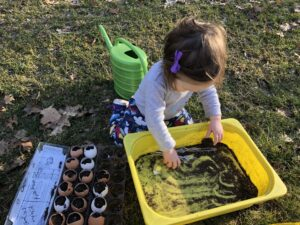 toddler planting seeds in eggshells for a Montessori outdoor activity.
