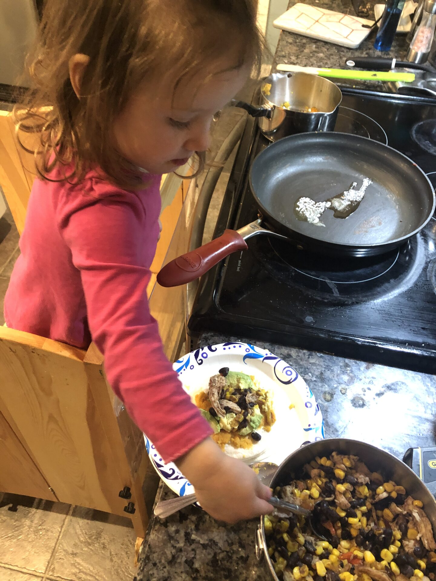 Toddler assembling her quesadillas for fun cooking activities for toddlers inspired by books.